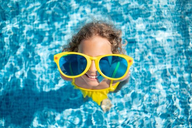 Glückliches kind im schwimmbad. draufsicht porträt