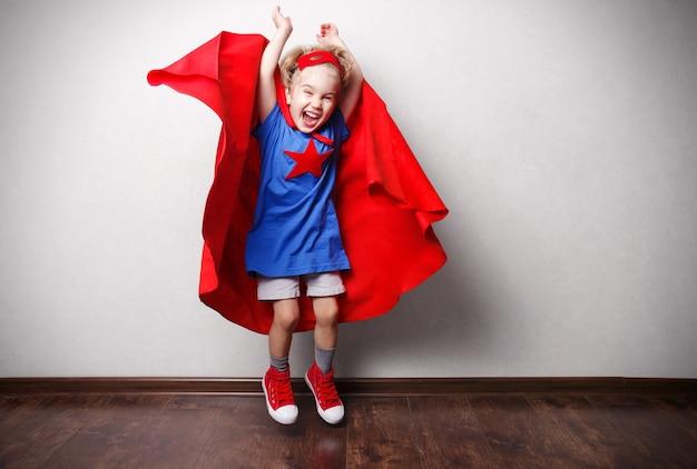 Glückliches kind im superheldenanzug gegen graue wand.