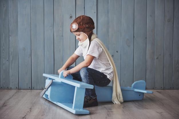 Glückliches kind im versuchshut, der mit hölzernem flugzeug gegen spielt. kindheit. fantasie, vorstellungskraft. urlaub