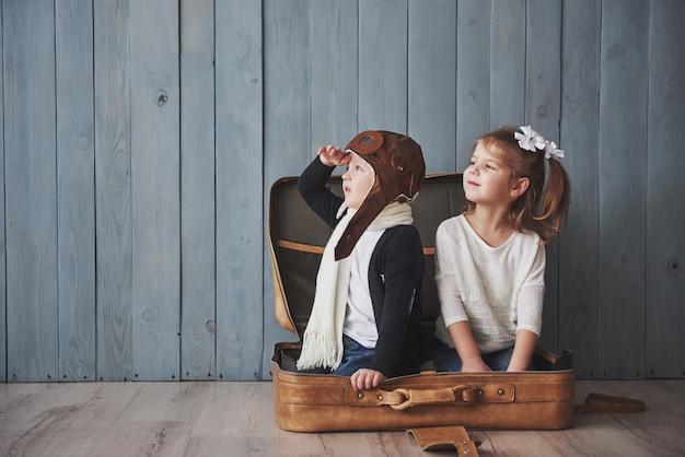Glückliches kind im versuchshut und in kleinem mädchen, die mit altem koffer spielen. kindheit. fantasie, vorstellungskraft. reise