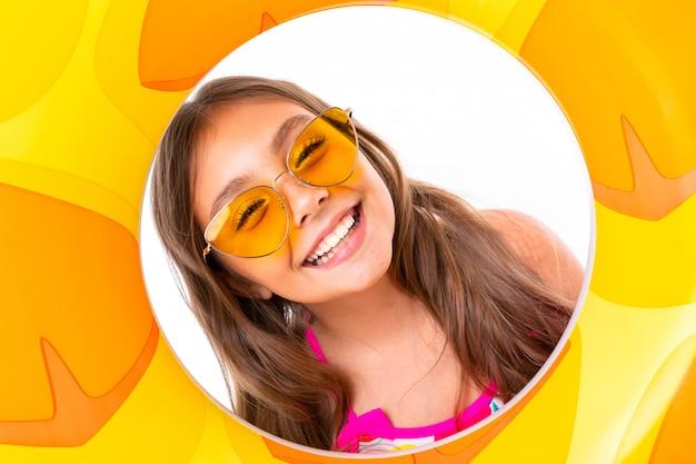 Glückliches kind in den sommerferien, mädchen in einem badeanzug mit einem breiten lächeln auf ihrem gesicht