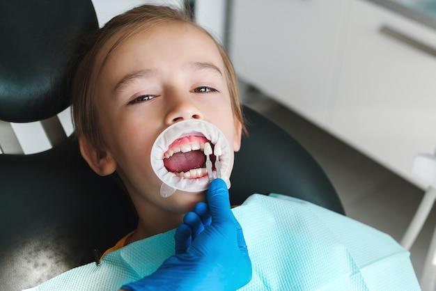 Glückliches kind in der klinik bei der zahnbehandlung zahnarzt kieferorthopädie junge patientin besuch beim spezialisten