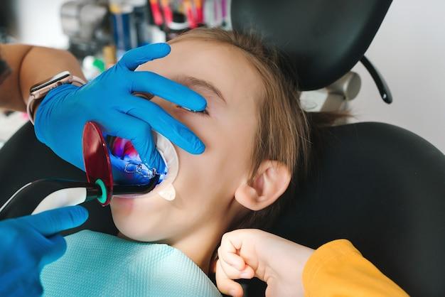 Glückliches kind in der klinik bei der zahnbehandlung zahnarzt untersucht jungenzähne