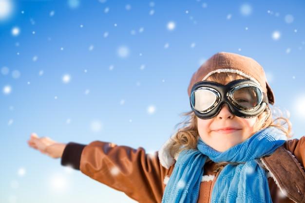 Glückliches kind in der rolle des piloten vor blauem winterhimmelhintergrund