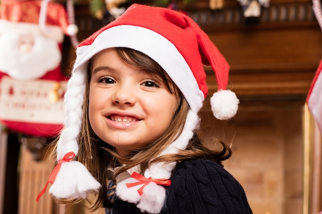 Glückliches kind in einem wohnzimmer auf weihnachten sitzen