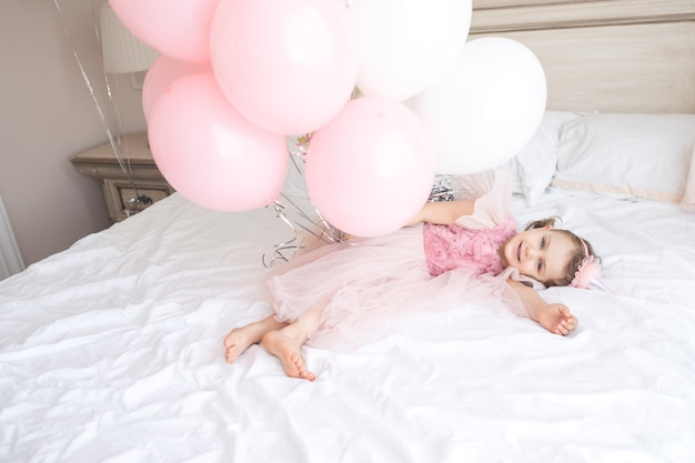 Glückliches kind in rosa festlichem kleid, geburtstagsmütze liegt auf einem gemütlichen weißen bett und hält banch-geburtstagsballons