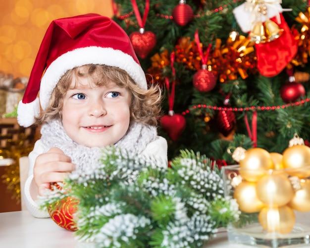 Glückliches kind in weihnachtsmütze gegen geschmückten weihnachtsbaum