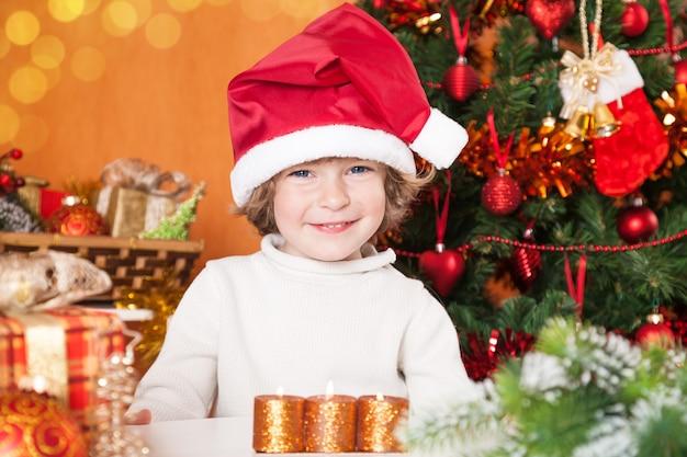 Glückliches kind in weihnachtsmütze gegen weihnachtsbaum mit dekorationen