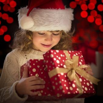 Glückliches kind in weihnachtsmütze öffnet weihnachtsgeschenkbox