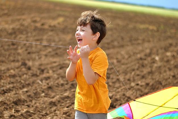 Glückliches kind lacht und lächelt, das mit dem fliegenden drachen am sonnigen sommertag auf dem feld spielt