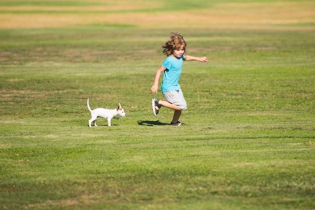 Glückliches kind läuft mit einem hund im freien.