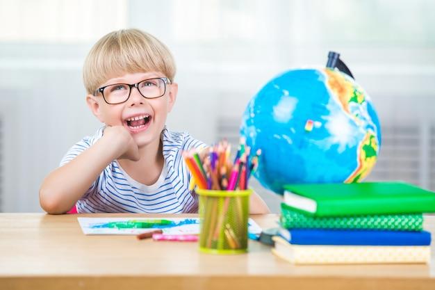 Glückliches kind lernen im klassenzimmer. lächelndes kind mit notizbüchern und büchern, die lektion lernen. fröhlicher junge in der schule.