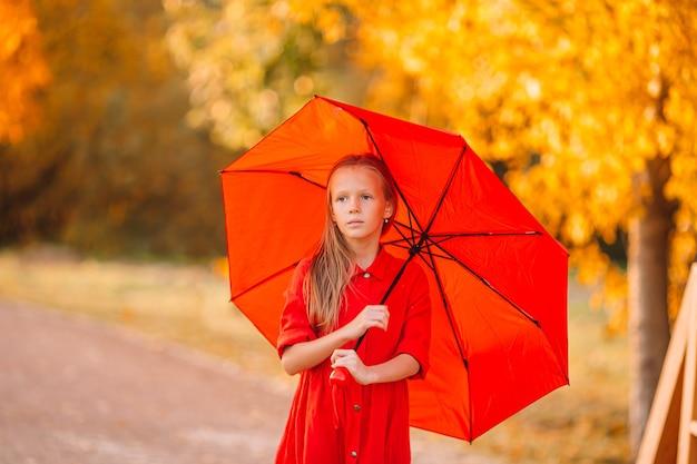 Glückliches kind mädchen lacht unter rotem regenschirm