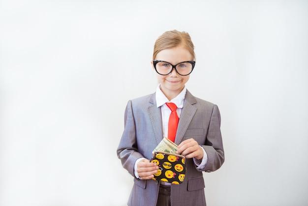 Glückliches kind mädchen steht in einem modischen anzug mit einer geldbörse in den händen Premium Fotos