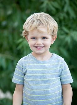 Glückliches kind mit blauem t-shirt im garten