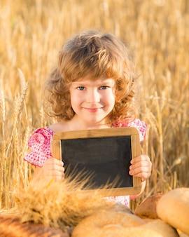 Glückliches kind mit brot im gelben herbstweizenfeld. kind hält tafel mit exemplar