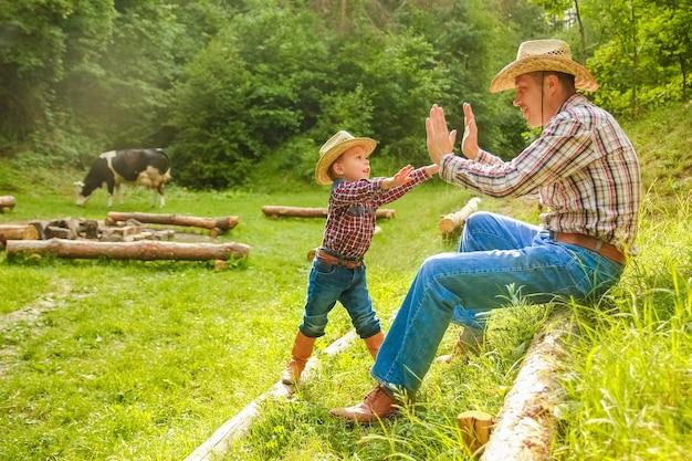 Glückliches kind mit cowboy-elternteil in der natur im feld