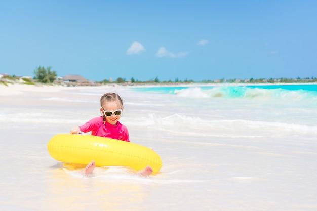 Glückliches kind mit dem aufblasbaren gummikreis, der spaß auf dem strand hat
