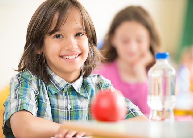 Glückliches kind mit der apfel- und wasserflasche, die im classrom und im lächeln sitzt