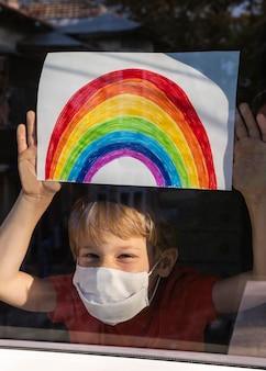 Glückliches kind mit der medizinischen maske, die regenbogenzeichen durch das fenster zu hause hält