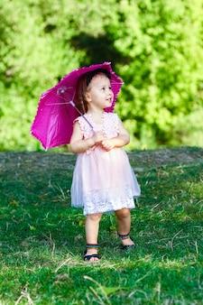 Glückliches kind mit einem regenschirm im park auf der natur