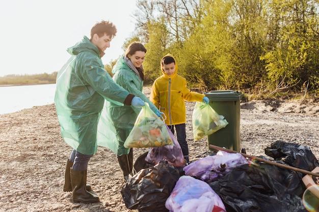 Glückliches kind mit eltern, die ein paket für plastikflaschen halten und gemeinsam die umweltverschmutzung retten