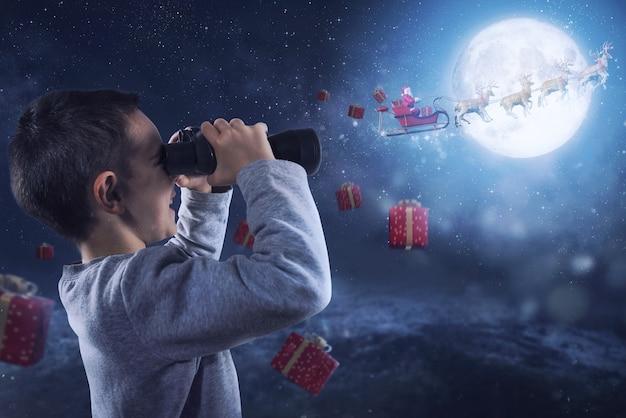Glückliches kind mit fernglasuhren santa claus, die mit rentieren fliegen