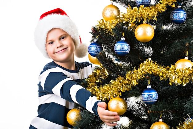 Glückliches kind mit geschenk nahe dem weihnachtsbaum