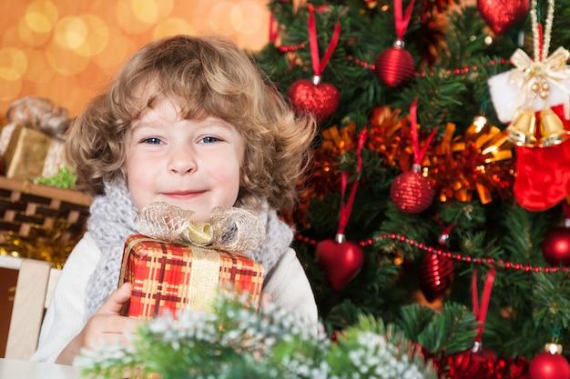 Glückliches kind mit geschenkbox gegen geschmückten weihnachtsbaum