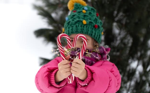 Glückliches kind mit großen zuckerstangen unter einem weihnachtsbaum. winterferienkonzept.