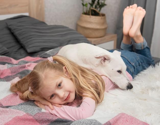 Glückliches kind mit hund. porträtmädchen mit haustier. mädchen und weißer jack russell