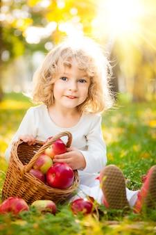 Glückliches kind mit korb mit roten äpfeln im herbstpark gegen goldenen sonnigen hintergrund