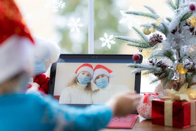 Glückliches kind mit medizinischer maske vater und mutter grüßen im video-chat