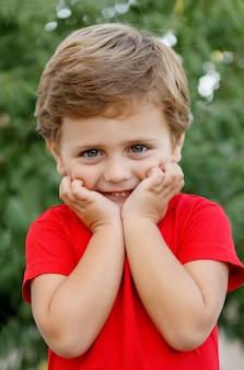 Glückliches kind mit rotem t-shirt im garten