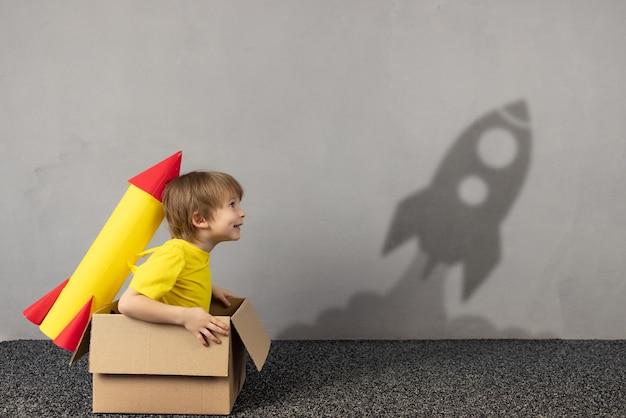 Glückliches kind mit spielzeugpapierrakete will fliegen