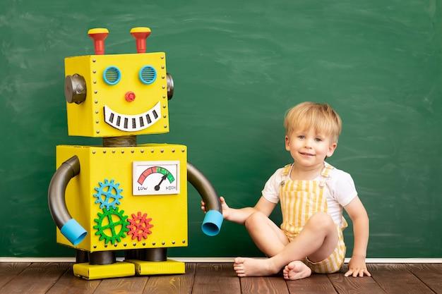 Glückliches kind mit spielzeugroboter im vorschulklassenzimmer.