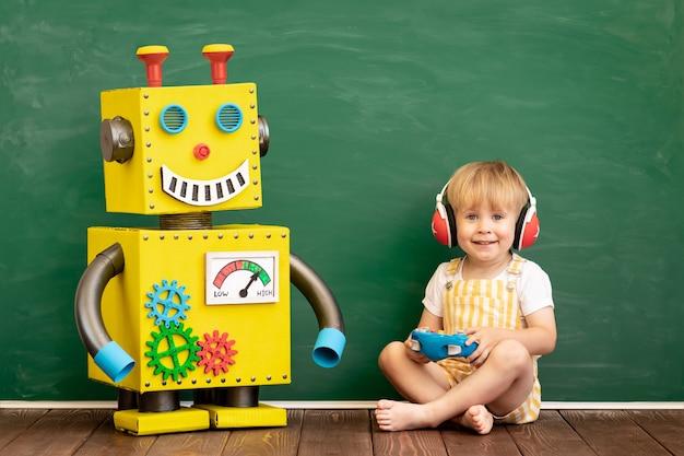Glückliches kind mit spielzeugroboter im vorschulklassenzimmer