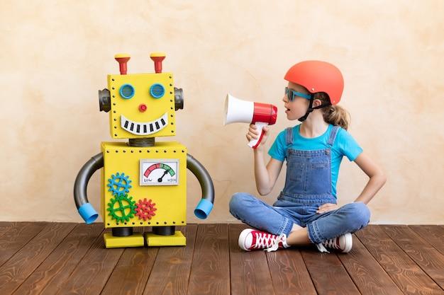 Glückliches kind mit spielzeugroboter