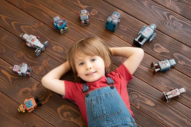 Glückliches kind mit spielzeugroboter.