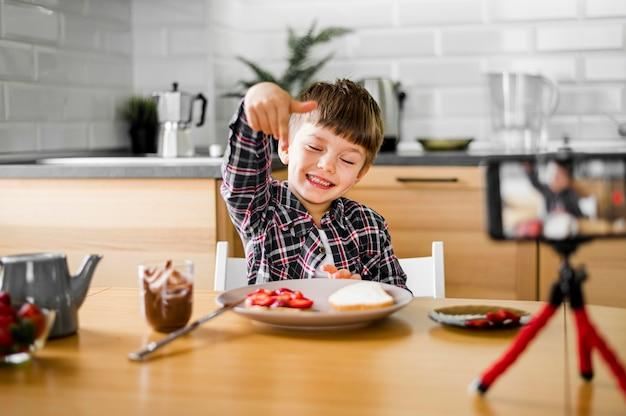 Glückliches kind mit telefon und essen