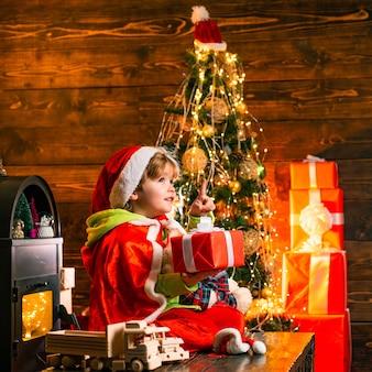 Glückliches kind mit weihnachtsgeschenk glückliches kind, das spaß mit geschenkweihnachtsdekorationen hat, wünschen ihnen frohe ...