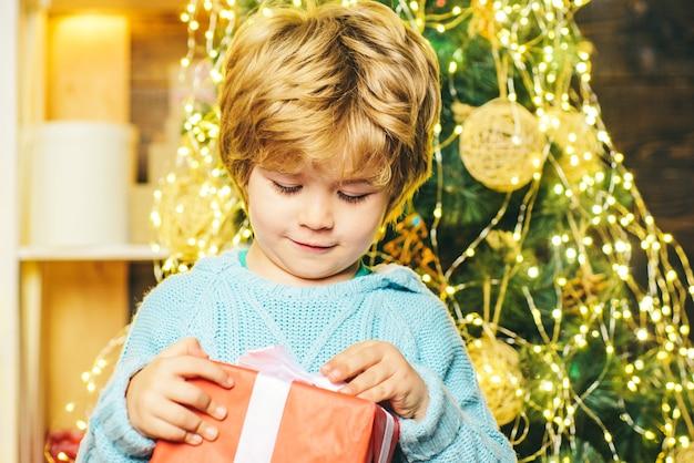Glückliches kind mit weihnachtsgeschenk. porträt des weihnachtsmannkindes mit geschenk, das kamera betrachtet. kind, das spaß hat
