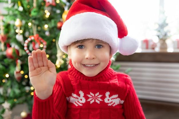 Glückliches kind mit weihnachtsmann-hut lustiger kindergruß im video-chat-weihnachtsfeiertagskonzept