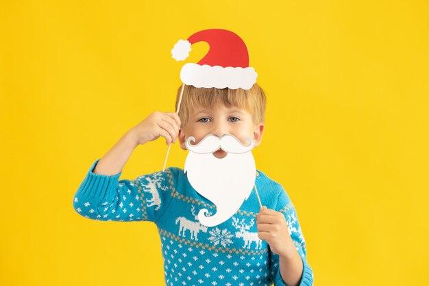 Glückliches kind mit weihnachtsmann-hut und bart-kind vor gelbem hintergrund