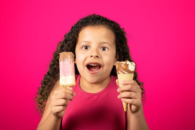 Glückliches kind mit zwei eiscreme in der hand mit flieder tisch, selektiver fokus.