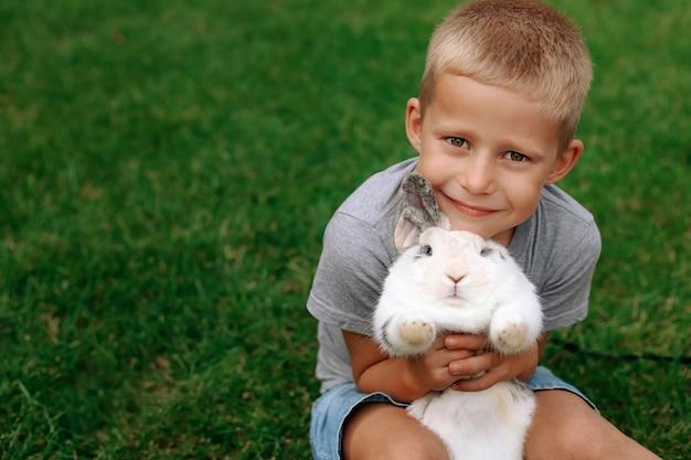 Glückliches kind sitzt auf dem grünen gras und hält ein kaninchen in seinen armen.