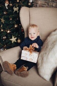 Glückliches kind sitzt auf dem sessel in der weihnachtsatmosphäre und lächelt