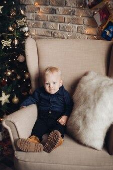 Glückliches kind sitzt auf dem sessel in der weihnachtsatmosphäre
