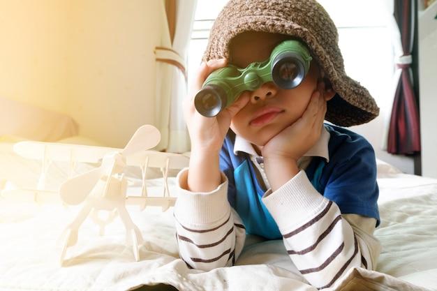 Glückliches kind spielt mit spielzeug flugzeug, kleine asiatische junge genießen reise, reise-und abenteuer-konzept