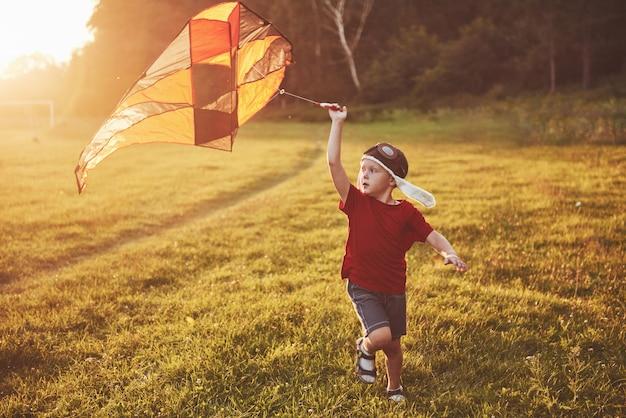 Glückliches kind starten sie einen drachen im feld bei sonnenuntergang. kleiner junge und mädchen in den sommerferien
